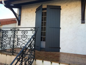 Volets battants gris semi ouvert pour porte fenêtre